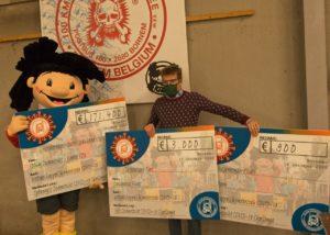 't Kadeeke houdt de cheques vast waarop de opbrengst van de 100Km Covid Challenge opstaat.